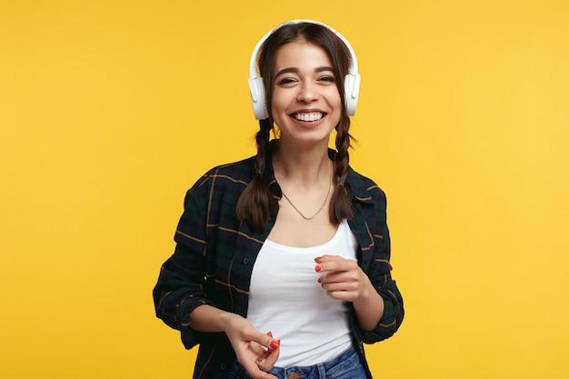 Gelukkig meisje met koptelefoon luistert muziek en lachend tegen gele muur