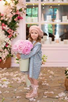 Gelukkig meisje met krullend haar in een jurk en in een baret met een boeket roze pioenrozen