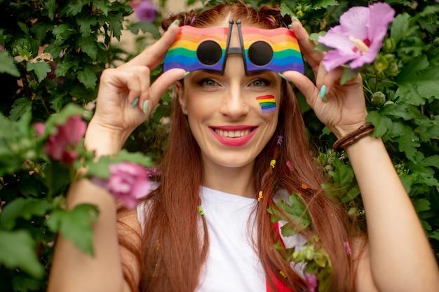 Gelukkig meisje met lgbt-vlag op haar gezicht dat regenboogglazen draagt en met glimlachend gezicht stelt