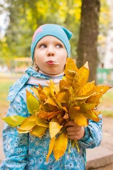 Gelukkig meisje met met boeket van de herfstbladeren in het park