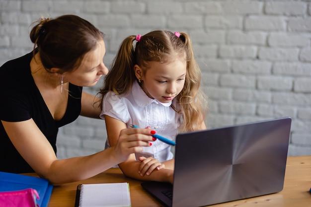 Gelukkig meisje met moeder die thuis online studeert. online leren of onderwijstechnologie concept
