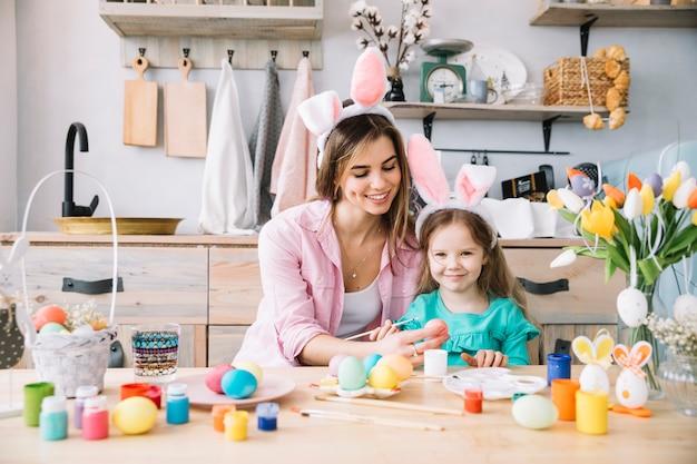 Gelukkig meisje met moeder schilderij eieren voor pasen