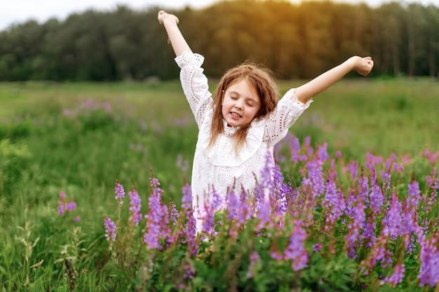 Gelukkig meisje met mooie bloemen in de zomer