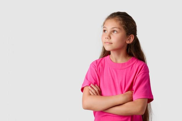 Gelukkig meisje met natuurlijk lang haar houdt handen gekruist en kijkt naar links en omhoog