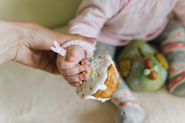 Gelukkig meisje met pasen-cake. baby houdt cupcake met veelkleurige lollies. paashaas cupcakes. pasen-cakes die met room, konijntjesgezicht worden verfraaid