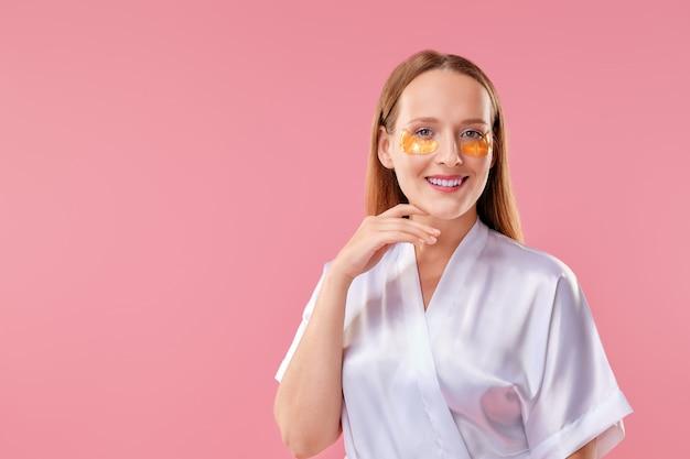 Gelukkig meisje met patch voor de huid rond de ogen glimlachend en haar kin aan te raken