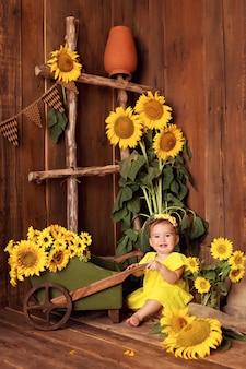 Gelukkig meisje met plezier en spelen onder bloeiende zonnebloemen in de buurt van de kar