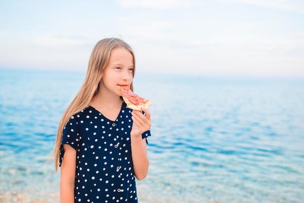 Gelukkig meisje met plezier op het strand en pizza eten