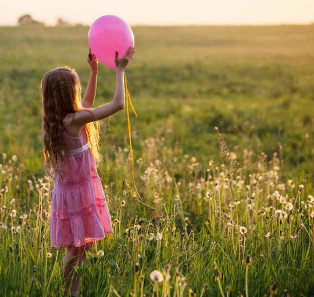 Gelukkig meisje met roze ballon buiten