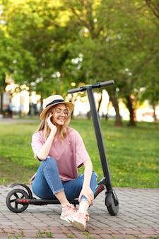 Gelukkig meisje met scooter in het park in de zomer