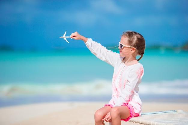 Gelukkig meisje met speelgoed vliegtuig in handen op witte zandstrand.