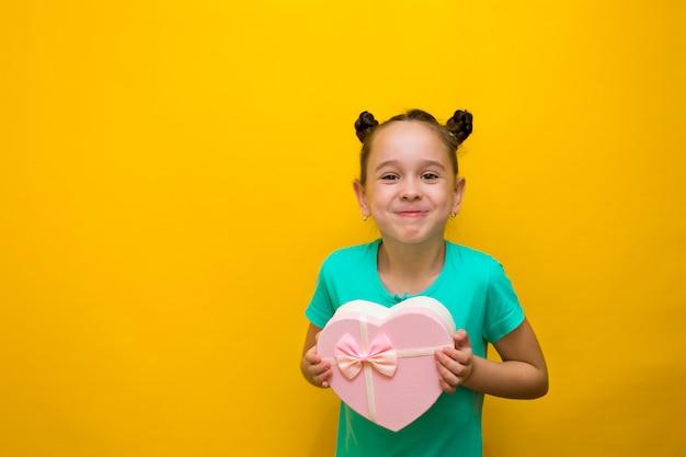 Gelukkig meisje met staarten status geïsoleerd over gele muurholding het winkelen roze zak. glimlacht nadenkend