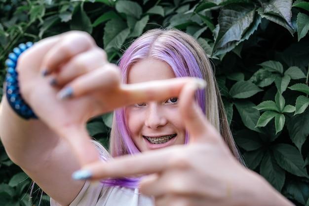 Gelukkig meisje met tandheelkundige beugels op donkergroene wijnstok achtergrond schattig kaukasisch meisje met roze haar we...