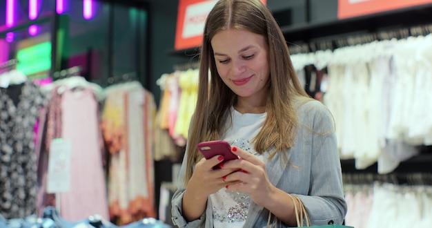 Gelukkig meisje met tassen met aankopen, glimlachend terwijl ze naar de telefoon in het winkelcentrum kijkt. goed nieuws ontvangen, bericht lezen, sms'en.