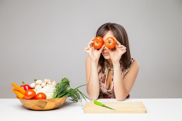 Gelukkig meisje met tomaten kijken. over grijze achtergrond.