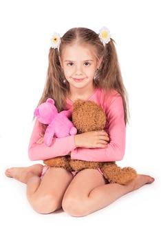 Gelukkig meisje met twee teddyberen die op witte achtergrond worden geïsoleerd