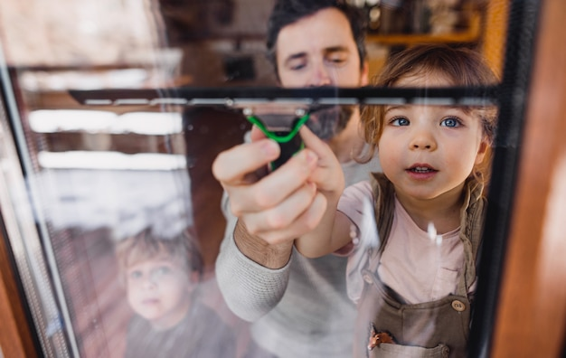Gelukkig meisje met vader die ramen thuis schoonmaakt, concept van dagelijkse klusjes. door glas geschoten.