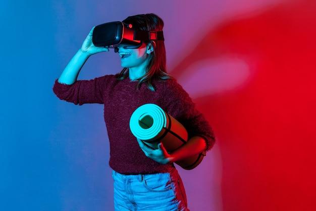 Gelukkig meisje met vr-bril headset met opgerolde yogamat, kijken naar fitnesscursussen