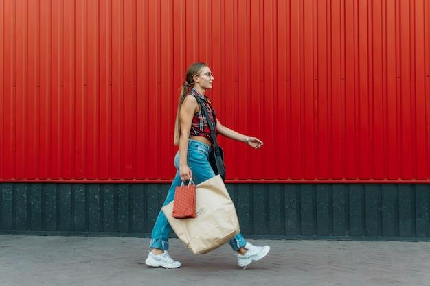 Gelukkig meisje met winkelen papieren zak op rode muur winkel achtergrond jonge vrouw met boodschappentas vol