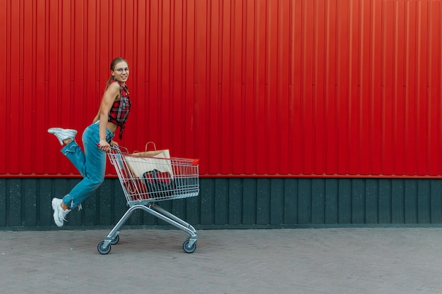 Gelukkig meisje met winkelwagentje op rode muur winkel achtergrond jonge vrouw duwen een winkelwagentje vol