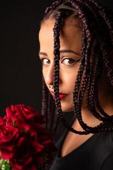 Gelukkig meisje, mooi meisje met een boeket rode rozen in haar hand, zwarte achtergrond, selectieve aandacht.