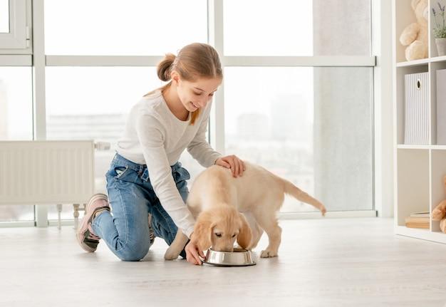 Gelukkig meisje naast het eten van puppy