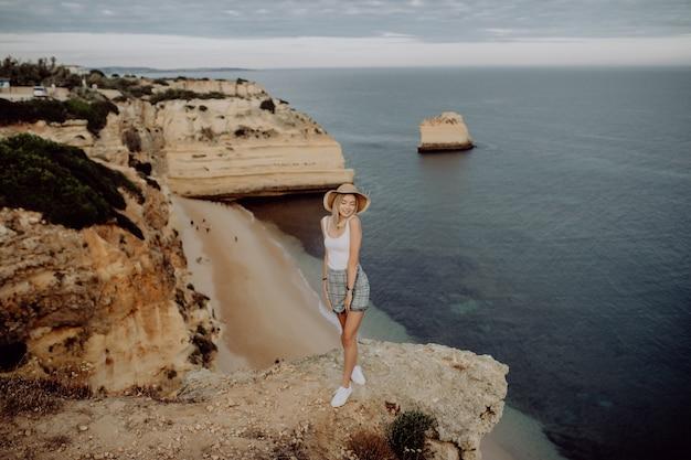 Gelukkig meisje op de rand van steen met panoramisch uitzicht op het strand.