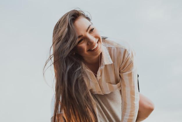 Gelukkig meisje op de schouders van haar vriendje glimlachend en gelukkig in de zomer in de natuur