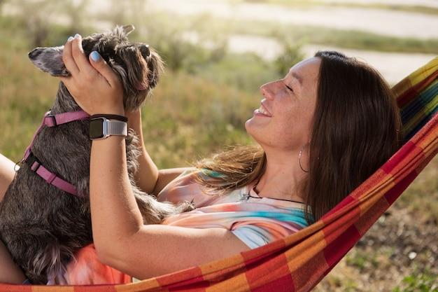 Gelukkig meisje op een picknick liggend in een hangmat met een kleine hond in haar armen, levensstijl, concept