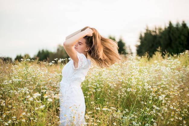 Gelukkig meisje op het veld kamille, zomer zonsondergang. in een witte jurk. rennen en draaien, de wind in mijn haar, levensstijl. vrijheid concept en hete zomer.