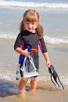 Gelukkig meisje op strand met kleurrijke gezichtsmaskers en snorkels,