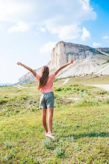 Gelukkig meisje op zomervakantie met de rots op de achtergrond