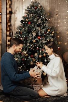 Gelukkig meisje opent kerstcadeau zittend in de buurt van de kerstboom.