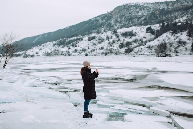 Gelukkig meisje permanent op een oever van de rivier in de winter en het nemen van foto op de telefoon. meisje dat van het uitzicht op de bevroren rivier geniet.