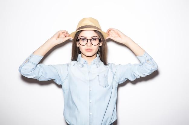 Gelukkig meisje poseren in strooien hoed, roze zomerblouse en blauwe short.