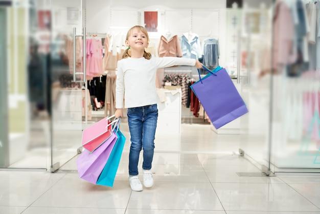 Gelukkig meisje poseren in winkelcentrum met veel tassen.