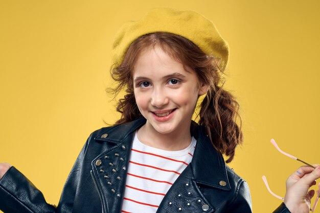 Gelukkig meisje poseren, mooi glimlachend kind in een stijlvol beeld en een leren jas op een gele muur