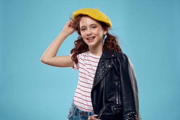 Gelukkig meisje poseren, mooi glimlachend kind in een stijlvol beeld en een leren jas