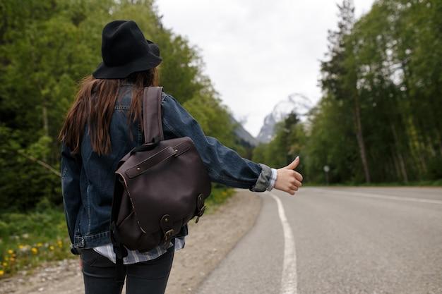 Gelukkig meisje rugzak in de weg en bos achtergrond, ontspannen tijd op vakantie concept reizen, kleur van vintage toon en zachte focus