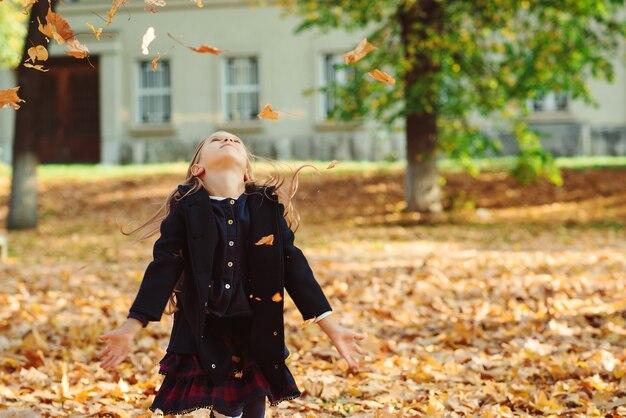 Gelukkig meisje spelen in de herfst en mooi meisje herfstbladeren gooien.