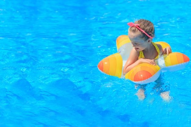 Gelukkig meisje spelen met kleurrijke opblaasbare ring in buitenzwembad op hete zomerdag. kinderen leren zwemmen. waterspeelgoed voor kinderen. kinderen spelen in tropische resort. familie strandvakantie.