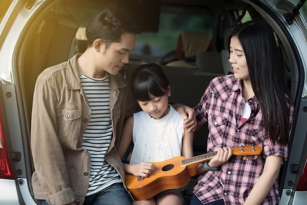 Gelukkig meisje spelen ukulele met aziatische familie zitten in de auto om te genieten van road trip en su