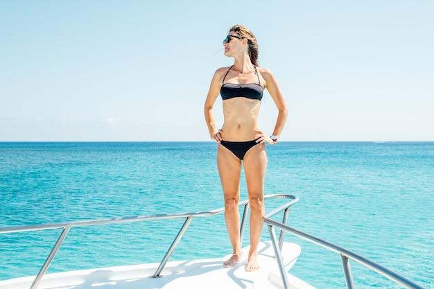 Gelukkig meisje staan op de boeg van een zeilboot, veel plezier met het ontdekken van eilanden in de tropische zee tijdens zomercruise aan de kust
