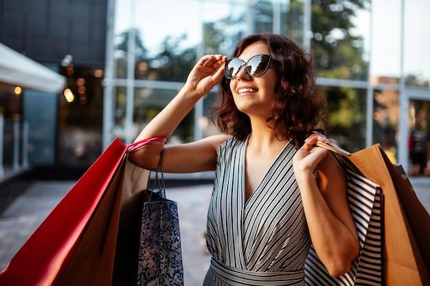 Gelukkig meisje staat in de buurt van boetiekwinkel met een paar tassen met aankopen.