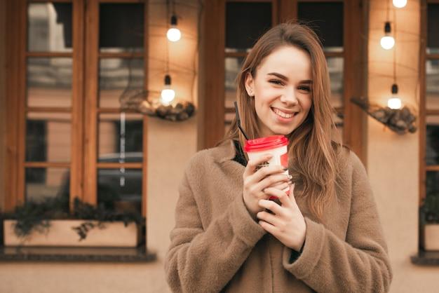 Gelukkig meisje staat in de straat met een kopje koffie in haar handen, kijkt naar de camera, glimlacht, poseert op de camera
