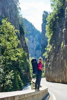 Gelukkig meisje staat op de bergweg van de roemeense bergen van de karpaten