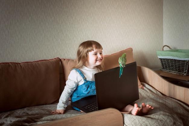 Gelukkig meisje thuis. huisdier. grasparkiet. laptop en gadgets. baby kijken naar tekenfilms, online games.