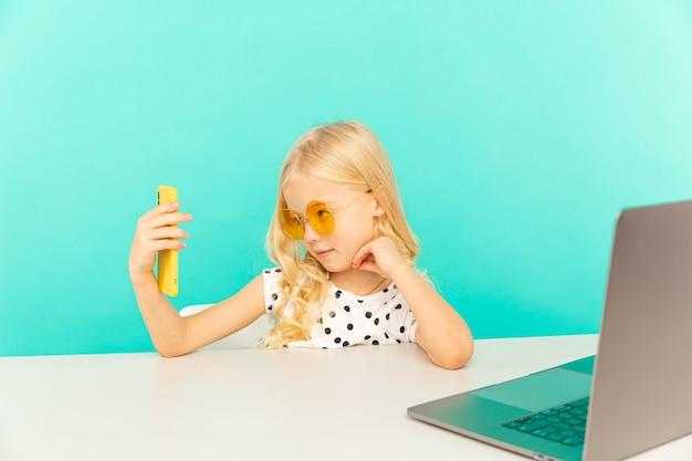 Gelukkig meisje thuis spreken voor camera voor vlog. kind dat zelffoto en video maakt als blogger, videozelfstudie voor internet opneemt.