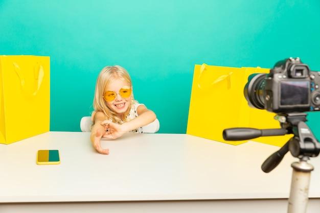Gelukkig meisje thuis spreken voor camera voor vlog. klein kind werkt als blogger, video-tutorial voor internet opnemen.