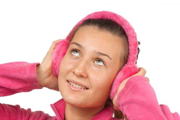Gelukkig meisje tiener in roze koptelefoon op wit wordt geïsoleerd